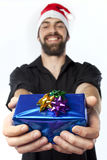 Presenting a gift. Handsome man with beard and santa hat holding out a gift towards the camera Stock Image