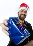 Presenting a gift. Handsome man with beard and santa hat holding out a gift towards the camera Stock Photography