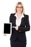 Presenting her brand new tablet. Beautiful mature businesswoman holding digital tablet and pointing it while standing isolated on white Stock Photo
