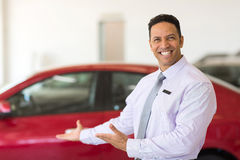Presenting new cars. Handsome vehicle salesman presenting new cars in showroom royalty free stock photo