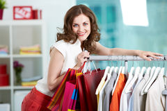 Presenting new collection. Portrait of happy woman looking at camera in clothing departmant Royalty Free Stock Photos