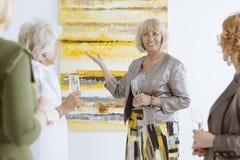 Presenting the painting. Happy elderly women presenting the painting in art gallery Royalty Free Stock Image