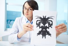 Presenting Rorschach inkblot. Serious psychologist showing paper with Rorschach inkblot Stock Photography