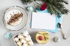 Presentkort- eller hälsningkort på en marmortabell med en kopp av cappuccino, efterrätt, maräng, tappningsked, arkivbild