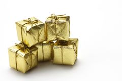 Presents. Close up of five small shiny christmas presents in golden wrapping with bows stack on each other in two levels on white background Stock Images