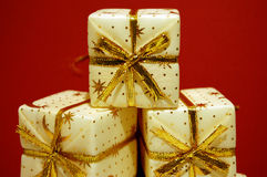 Presents. Three packages with golden bows on a red background Royalty Free Stock Photos