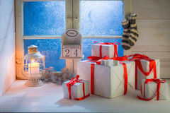 Presents for Christmas with a frozen blue window and candlelight Royalty Free Stock Image