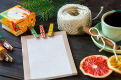 Presents for friends and family in orange and green paper, notepad, cup of coffee on the wooden background. shopping royalty free stock photo