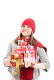 Presents and gifts for the holidays. Beautiful young woman holding presents wearing winter clothes isolated on white background Royalty Free Stock Images