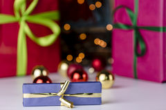 Presents and glitter balls. Festive presents wrapped in magenta, red and blue. The golden bowknot is in focus and does correspond with the twinkles of the Stock Photography