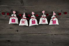 Presents with hearts hanging on wooden background for celebrations.