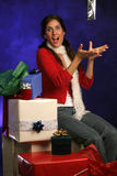 Presents from heaven. Surrounded by gifts lady catches her package as it falls from above with misty blue background Stock Image