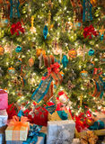 Presents Holiday Christmas Tree, Colors. Lots of colors can be seen with holiday presents under the Christmas tree. Each gift is wrapped in color wrapping paper Stock Photo