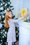 Presents for new year. Pretty child girl is standing near the Christmas tree in a beautiful room and holding a gift box. Merry Christmas and Happy New Year stock photos