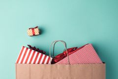 Presents in paper bag. Top view of wrapped presents in paper bag on blue tabletop Stock Photos