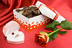 Presents on the red velvet. Opened candy box with chocolate and rose on the red background. Gold ring in the box Stock Photos