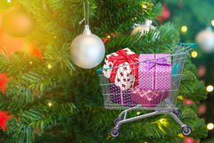 Presents ribbon gift box in shopping trolley cart with christmas tree and balls decorations and blurred lights Stock Image