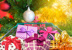 Presents ribbon gift box in shopping trolley cart with christmas tree and balls decorations and blurred lights Stock Photo