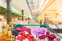 Presents ribbon gift box in shopping trolley cart. In shopping mall Stock Image