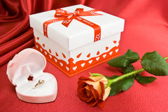 Presents and rose. Gift and rose on the red background. Gold ring in the opened box Royalty Free Stock Photography