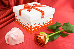 Presents and rose. Present and rose on the red background. Box for the ring is closed Royalty Free Stock Images