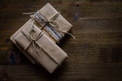 Presents in rustic wrap, wood background Royalty Free Stock Photography