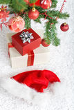 Presents and santa hat under the christmas tree Stock Photos
