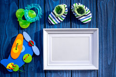 Presents set for baby shower with frame blue wooden background top view mockup