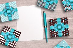Presents with sheet of paper, pen and pencil over desk Royalty Free Stock Image