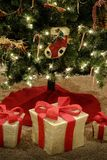 Presents under Bright Decorated Christmas Tree Red Ribbon Wrapped Gifts stock images