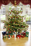 Presents under an illuminated christmas tree Royalty Free Stock Image