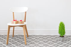 Presents on a white chair, and little green tree Stock Photo