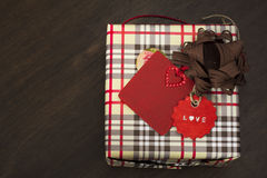 Presents wrapped in checkered paper and brown ribbon with red la Stock Photos