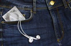 Preservativi in pacchetto e cuffie in jeans Fotografia Stock Libera da Diritti