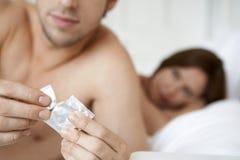 Preservativo di apertura dell'uomo con la donna a letto Immagine Stock