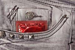 Preservativo nas calças de brim cinzentas Imagem de Stock