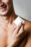 Preservativo sonriente atractivo joven de la explotación agrícola del hombre Imagen de archivo libre de regalías