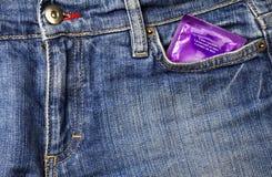 Preservativo y pantalones vaqueros Fotografía de archivo libre de regalías