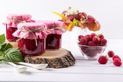 Preserved berry. Glass jar with homemade raspberry jam. On a white background Royalty Free Stock Image
