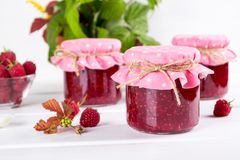 Preserved berry. Glass jar with homemade raspberry jam. On a white background stock photos