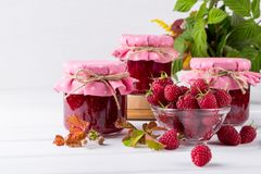 Preserved berry. Glass jar with homemade raspberry jam. On a white background Stock Image