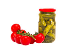 Preserved cucumbers jar and fresh tomato bunch Stock Photo