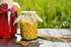 Preserved fruit, sour cherries compote. Canned fruit on wooden table Royalty Free Stock Photos