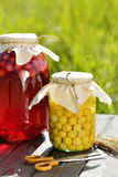 Preserved fruit, sour cherries compote. Canned fruit on wooden table Royalty Free Stock Photo