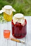 Preserved fruit, sour cherries compote. Canned fruit on wooden table Stock Image