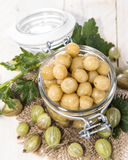 Preserved Gooseberries. Portion of preserved Gooseberries with some fresh fruits stock photo