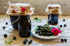 Preserved homemade black currant jam in glass jars on light wooden table. Fresh berries and green leaves, white vintage plate Stock Photography