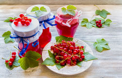 Preserved homemade red currant jam in glass jars on white wooden table. Fresh berries and green leaves, vintage plate Stock Photo