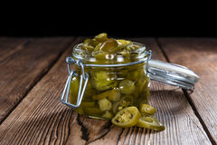 Preserved Jalapenos. Portion of preserved Jalapenos (close-up shot) on wooden background Royalty Free Stock Image