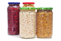 Preserved legumes. Some jars with different preserved legumes, such as white beans, red beans, lentils and chickpeas on a white background royalty free stock photography